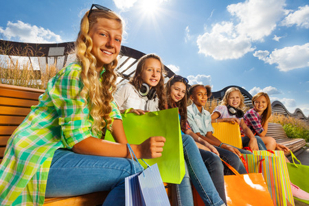 Group of happy girls with shopping bags sitting