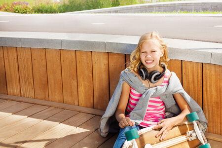Blond girl wears sweatshirt over shoulders sitting photo