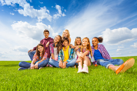 Happy international children sit on green meadow photo