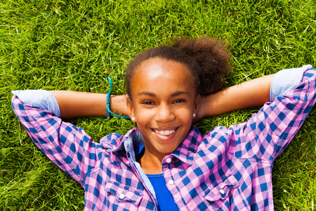 girl portrait: Smiling African girl with in summer lays on grass Stock Photo