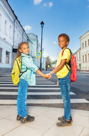 Two African kids hold hands, stand near crossroad photo