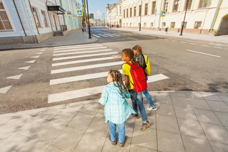 ni�os sosteniendo un cartel: Ni�os cuidado al cruzar la calle Foto de archivo