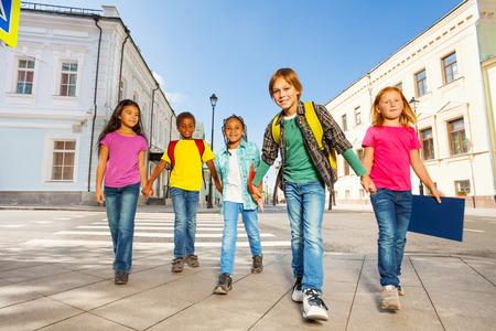 paso de peatones: La diversidad de los niños caminando a manos sosteniendo juntos Foto de archivo