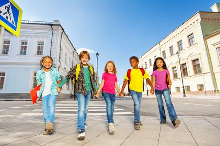 paso de cebra: Escolares internacionales a pie y se dan la mano Foto de archivo