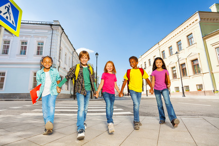 International schoolchildren walk and hold hands Banco de Imagens