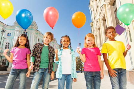 weather balloon: Multinational children with balloons standing Stock Photo