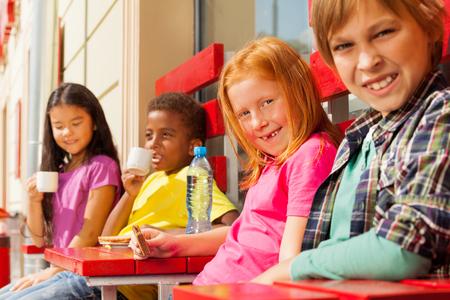 Happy international kids sit in outside cafe photo