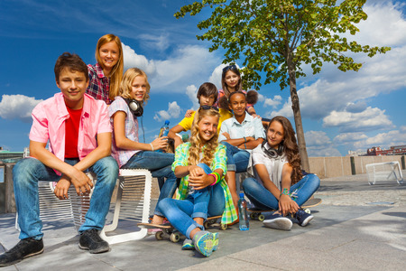 multinational: Happy friends sit on chairs of the embankment