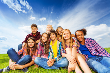 multinational: Happy friends sitting on green meadow Stock Photo