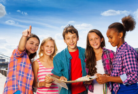 Smiling kids with map at city tours stand together Stock Photo