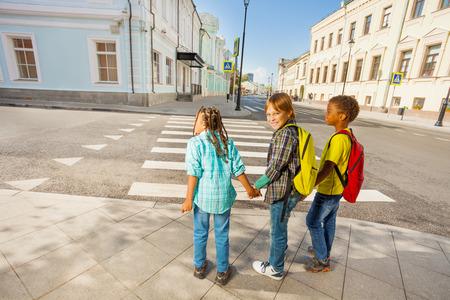 Drie kinderen hand in hand staan op straat