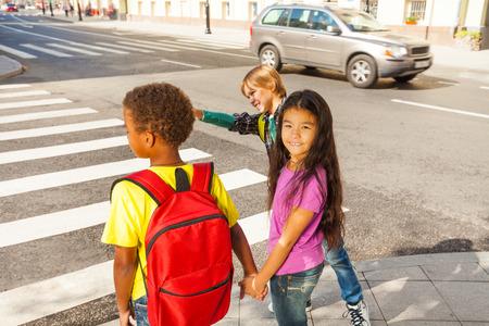Drie internationale kinderen klaar om de weg over te steken
