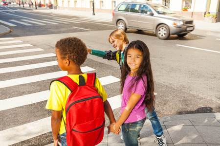 cross walk: Three international kids ready to cross road