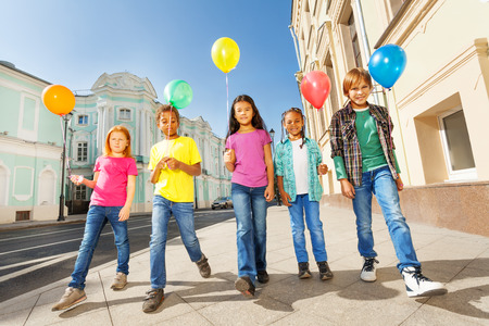 Walking children diversity with colorful balloons Stock Photo