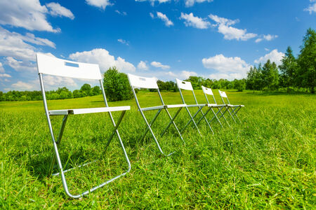 White chairs standing in a row on green grass photo