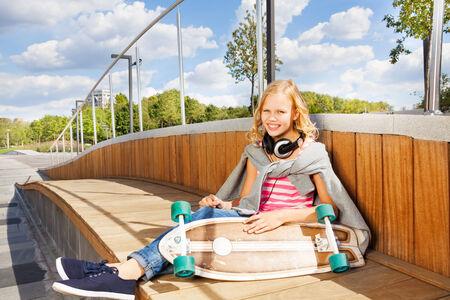 Cute girl holds skateboard wearing headphones photo