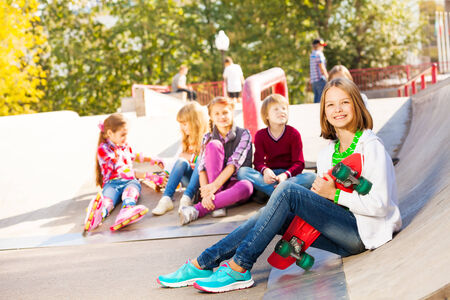 sitting on the ground: Girl with skateboard and her mates sitting