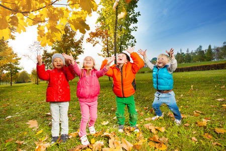 Team of children playing with flying leaves Stock Photo