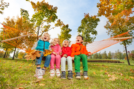 Group of happy children sitting on hammock in park photo