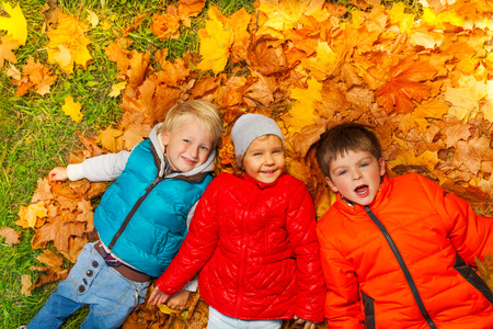 children clothing: Happy kids laying together on the autumn leaves
