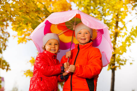 couple in rain: Boy and girl hold umbrella together under rain Stock Photo