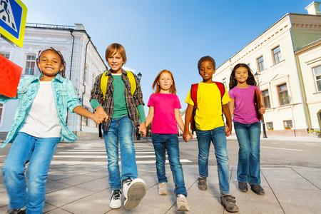 niños sosteniendo un cartel: Niños Internacionales llevan bolsas y caminan en fila Foto de archivo