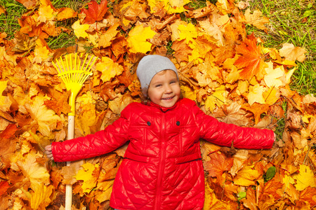 rake: Happy girl laying on the autumn leaves with rake