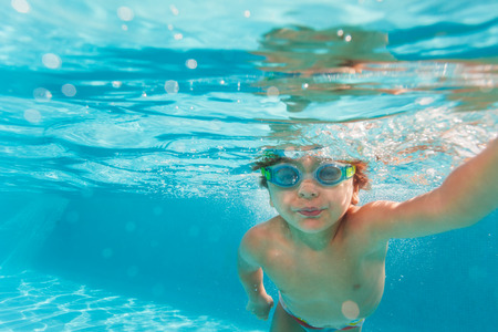 Small boy swimming wearing goggles under water photo