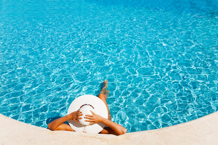 Lady with white hat laying in the blue water photo