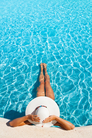 Girl holding white hat with hands in swimming pool Banque d'images