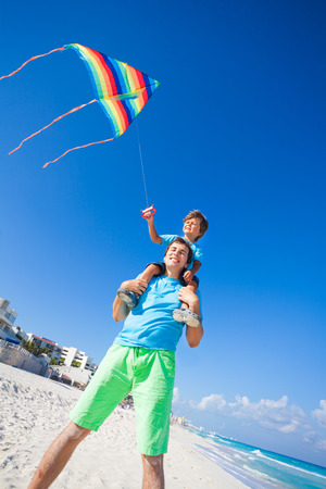 Boy sits on shoulders of dad holding flying kite photo