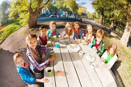 wide angle lens: Wide angle lens view of children drinking tea Stock Photo