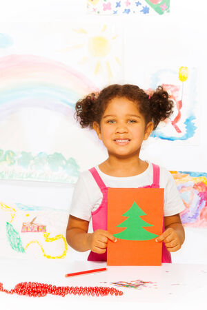 Girl holds carton card with Xmas tree and stands photo