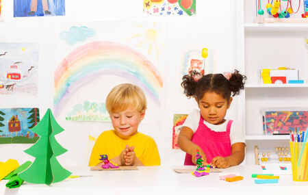 Boy and girl craft together forms of playing dough photo