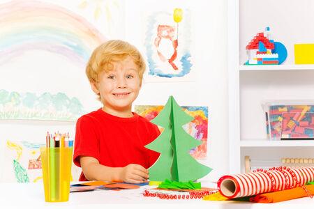 Positive cute small boy holding carton Xmas tree photo