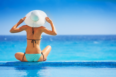 Young woman sitting from back with white hat in striped swimsuit on the ocean coast during holidays summer time
