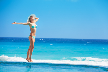 cuerpo femenino: Mujer de pie con el sombrero blanco en la costa del oc�ano Foto de archivo