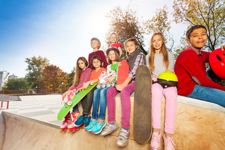 Sitting children with skateboards and helmet