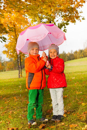 couple in rain: Happy boy and girl with umbrella standing together