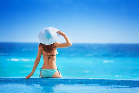 Vrouw van achter met witte hoed zit op kust