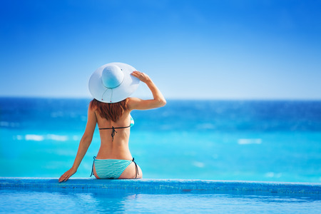 bikinis: Woman from back with white hat  sits on coast