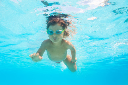 underwater sport: Small boy with goggles swims alone under water