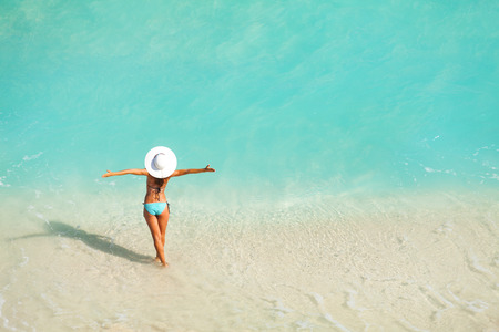 summer holiday bikini: Top view of woman with white hat standing in ocean Stock Photo