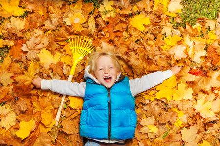 Menino de riso que coloca nas folhas de outono com ancinho