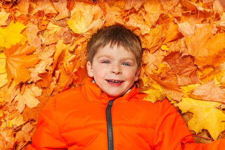close up view: Close up view of happy boy laying on autumn leaves Stock Photo