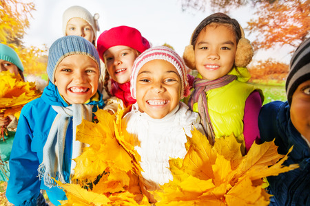 Close up view of happy cute kids with leaves bunch
