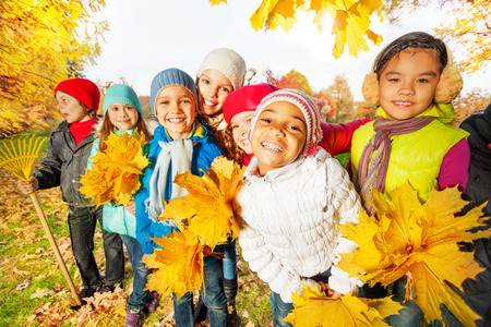 Team of kids with rake and yellow leaves  bunches