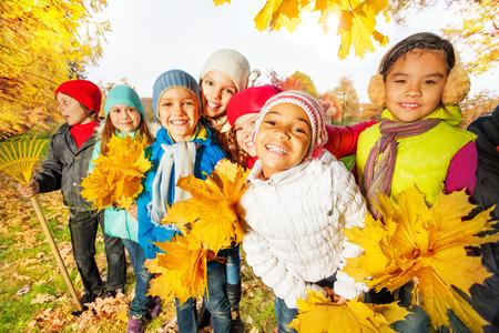 Team van kinderen met hark en gele bladeren trossen
