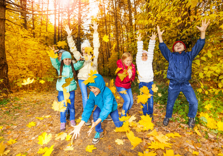 Happy children playing with flying leaves photo