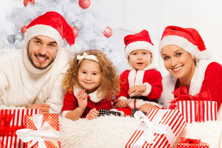 Family of four with presents and Christmas tree photo